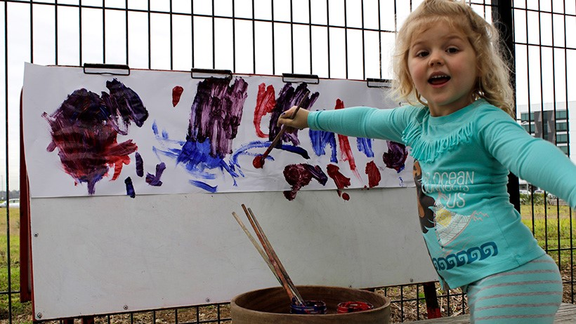 girl painting at daycare