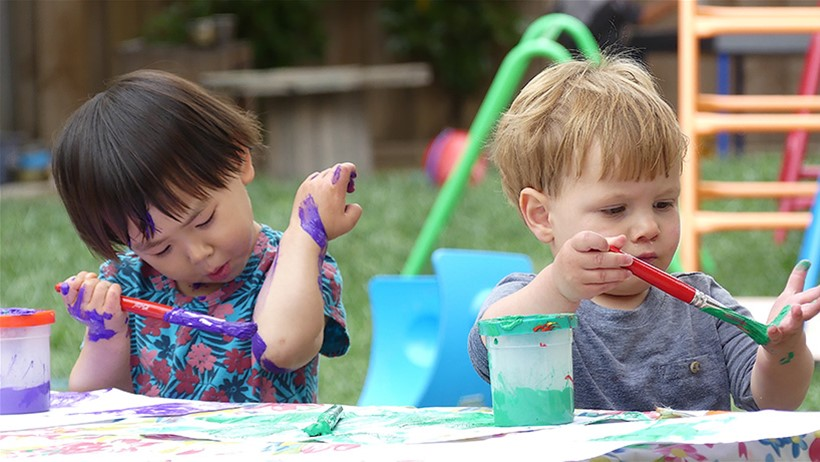 children painting hands at childcare